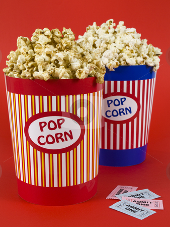 Doble date night stock photo, Two popcorn buckets over a red background. Movie stubs sitting aside. by Ignacio Gonzalez Prado