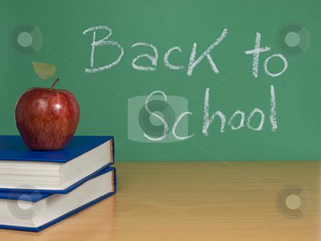 Back to school stock photo, Back to school written on a chalkboard with an apple over books. by Ignacio Gonzalez Prado