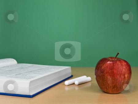 Blank chalkboard stock photo, A blank chalkboard with an apple, a book and some chalks. by Ignacio Gonzalez Prado