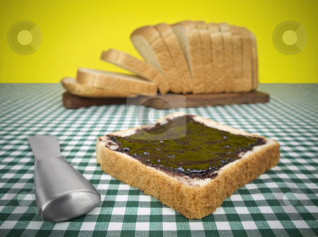 Breakfast time stock photo, A slice of bread spread with jam. Loaf of bread on the background. by Ignacio Gonzalez Prado