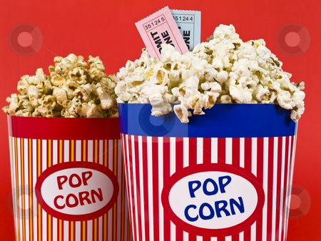 Fun dating stock photo, Two popcorn buckets over a red background. Movie stubs sitting over the popcorn. by Ignacio Gonzalez Prado