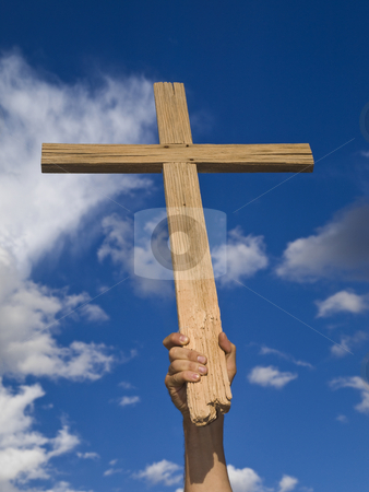 Keeping the faith stock photo, A man?s hand keeping a wooden cross high in the sky. by Ignacio Gonzalez Prado
