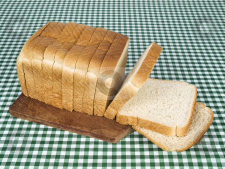 Sliced bread stock photo, A sliced loaf of bread served on a wooden cutting board. by Ignacio Gonzalez Prado