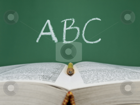 ABC stock photo, ABC written on a chalkboard with an open book and a pencil on foreground. by Ignacio Gonzalez Prado