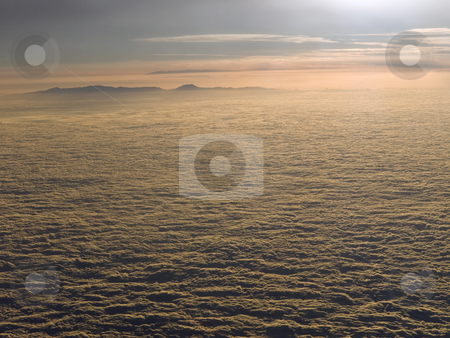 Bouncing off the clouds stock photo, The sun declines above the clouds. A mountain is looming on the background. by Ignacio Gonzalez Prado