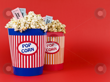 Fun night for four stock photo, Two popcorn buckets over a red background. Movie stubs sitting over the popcorn. by Ignacio Gonzalez Prado