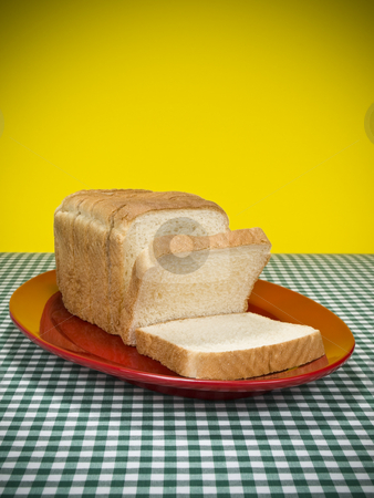 Sliced bread stock photo, A loaf of sliced bread served on a red platter. by Ignacio Gonzalez Prado