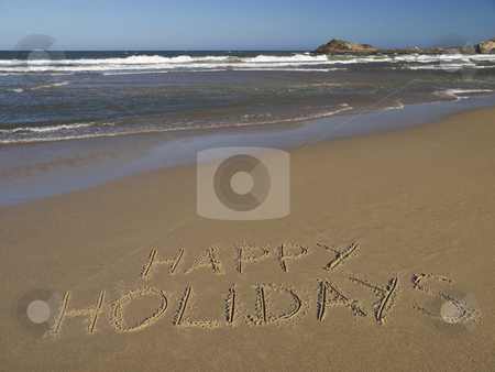 Happy holidays stock photo, Happy holidays written on the sand beside the ocean. by Ignacio Gonzalez Prado