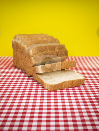 Sliced bread stock photo, Sliced loaf of bread over the table. by Ignacio Gonzalez Prado