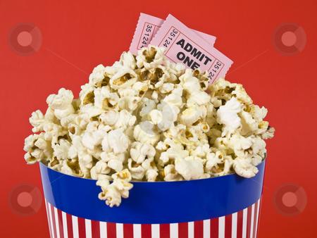 Popcorn and movies stock photo, A popcorn bucket over a red background. Movie stubs sitting over the popcorn. by Ignacio Gonzalez Prado