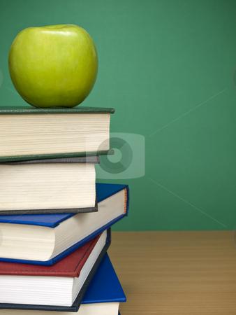 Blank chalkboard stock photo, An apple on top of a pile of books. Blank chalkboard on the background. by Ignacio Gonzalez Prado