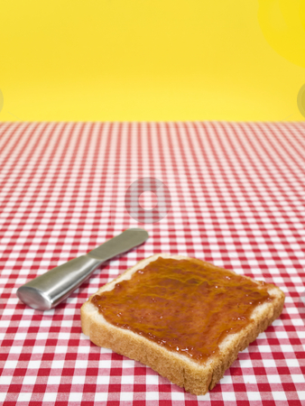 One toast stock photo, A slice of bread spread with jam and a knife over the table. by Ignacio Gonzalez Prado