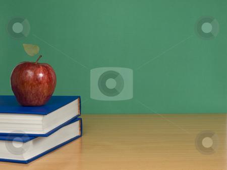 Blank chalkboard stock photo, A blank chalkboard with an apple over books. by Ignacio Gonzalez Prado