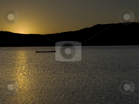 Magic hour stock photo, The sun behind the mountains is reflected over the lake surface, beside an abandoned boat. by Ignacio Gonzalez Prado