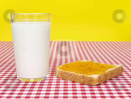Quick breakfast stock photo, A glass of milk and a toast spread with jam over the table. by Ignacio Gonzalez Prado