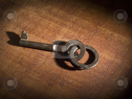 Old key stock photo, An old key on a keyring over a wooden table. by Ignacio Gonzalez Prado