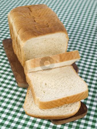 Sliced bread stock photo, A sliced loaf of bread served on a wooden cutting board. by Ignacio Gonzalez Prado