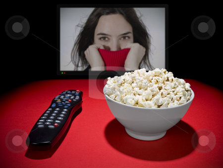 Movies at home stock photo, A popcorn bowl and a remote control. A wide TV screen as a background. by Ignacio Gonzalez Prado