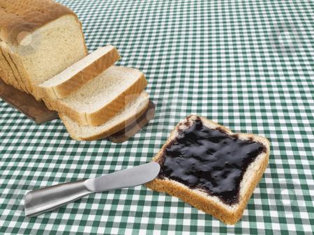 Spread the jam stock photo, A slice of bread spread with jam beside the loaf of bread. by Ignacio Gonzalez Prado