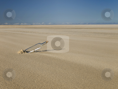Lost in a desert stock photo, A bottle with a message inside is abandoned in the desert. by Ignacio Gonzalez Prado