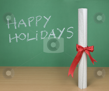 Happy holidays stock photo, Happy holidays written on a chalkboard with a diploma on forefround. by Ignacio Gonzalez Prado