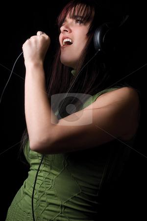 Fashion model - air singning stock photo, Twenty something fashion model air singing to music with big headphone by Yann Poirier