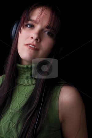 Fashion model - listening to music stock photo, Twenty something fashion model listening to music with big headphone by Yann Poirier