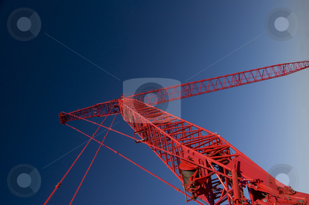 Extreme Red Crane stock photo, Extremely large red crane create lines against a blue sky. by Charles Buegeler