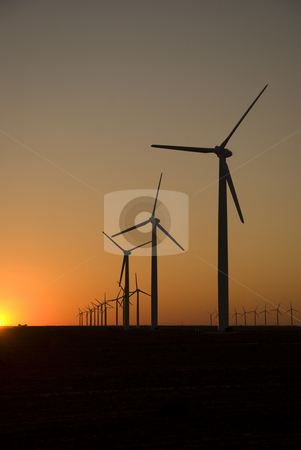 Alternative Energy stock photo, Sunset silhouette view of a wind turbine field. by Charles Buegeler