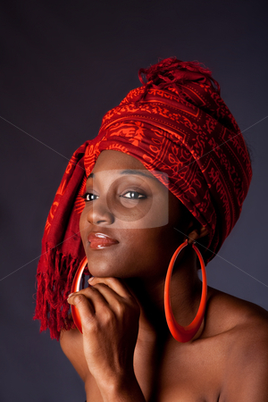 African woman with headwrap stock photo, Beautiful African-American woman wearing a traditional tribal red orange head scarf and big orange hoop earrings, supporting her chin with hand, isolated. by Paul Hakimata