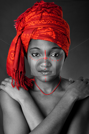 Tribal African woman with headwrap stock photo, Beautiful traditional African-American woman wearing a authentic tribal red orange head scarf and red dotted makeup, heaving arms crossed on chest, isolated. by Paul Hakimata