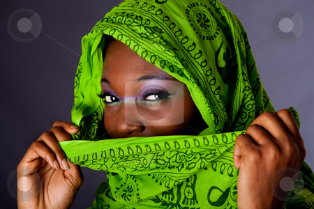 African woman with scarf stock photo, The face of an innocent beautiful young African-American woman covering her mouth with green headwrap and purple-green makeup, isolated by Paul Hakimata
