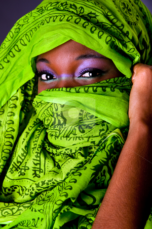 African woman with scarf stock photo, The face of an innocent beautiful young African-American woman covering her mouth showing only her eyes with green headwrap and purple-green makeup, isolated by Paul Hakimata