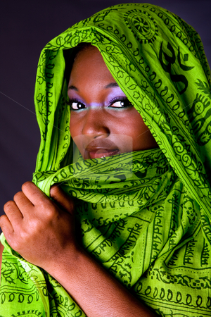 Shy African woman with scarf stock photo, The face of an shy innocent beautiful young African-American woman covering her mouth with green headwrap and purple-green makeup, isolated by Paul Hakimata
