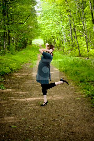 Dancing In the Woods stock photo, A young woman posing on a wooded path. by Todd Arena