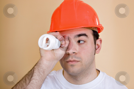 Light Bulb Energy Savings stock photo, A young construction worker or home builder holding an energy saving compact fluorescent light bulb up to his eye. by Todd Arena