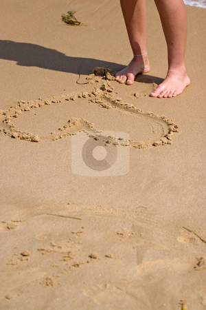 Heart In The Sand stock photo, A young woman stands on the sandy shore by the heart she drew in the sand. by Todd Arena