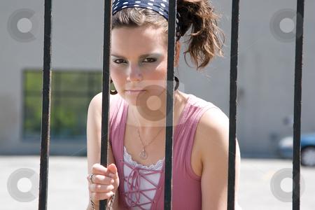 Fashion model in jail stock photo, Twenty something fashion with mad expression behind bar by Yann Poirier