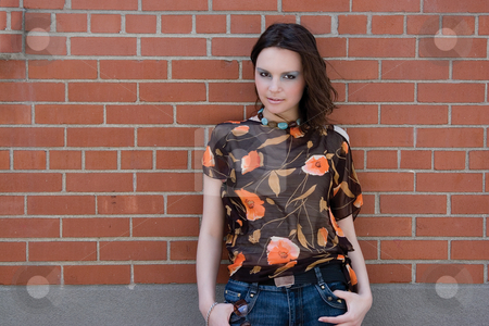Girl hanging on brick wall stock photo, Twenty something fashion model giving a piercing look to the camera while hanging on a brick wall by Yann Poirier