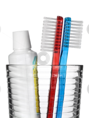 Toothbrush and toothpaste stock photo, Two toothbrushes and a tube of toothpaste in a glass over white background. by Ignacio Gonzalez Prado