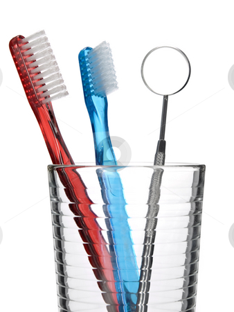 Oral tools stock photo, Two toothbrush and a mouth mirror in a glass. by Ignacio Gonzalez Prado