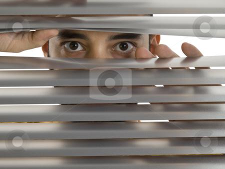 Peeping Tom stock photo, A man looks to the camera through the blinds. by Ignacio Gonzalez Prado