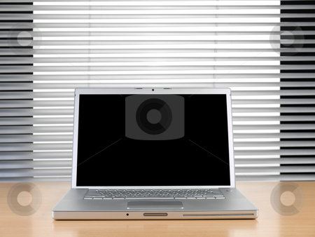 Laptop and blinds stock photo, A laptop on a table at a modern office. by Ignacio Gonzalez Prado