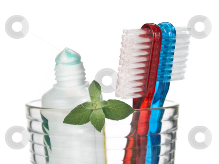 Minty breath stock photo, Toothbrushes, toothpaste and mint leaves in a glass over white background. by Ignacio Gonzalez Prado
