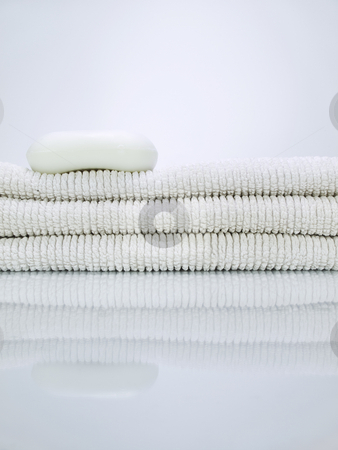 Soap and towels stock photo, A soap over a pile of towels. by Ignacio Gonzalez Prado