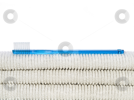 Toothbrush and towels stock photo, A blue toothbrush over a few white towels. by Ignacio Gonzalez Prado
