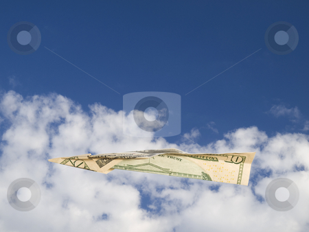 Flying high stock photo, A ten dollars bill airplane flying over the clouds on a blue sky. by Ignacio Gonzalez Prado
