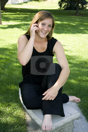 Beautiful Girl in the Park in a Black Dress Talking on the Phone stock photo, Close up on a Beautiful in a Black Dress sitting on the Bench Talking on a Cell Phone by Mehmet Dilsiz