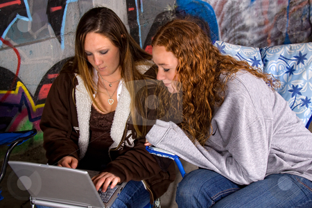 Girls On the Laptop stock photo, Girls sitting down in a grunge building with grafittis on the wall by Mehmet Dilsiz