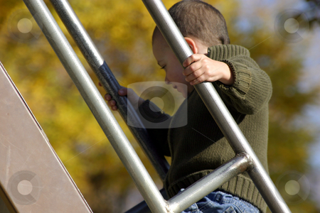 Kid Climbing Up the Slider with Hand in Focus stock photo, Kid Climbing Up the Slider with Hand in Focus by Mehmet Dilsiz